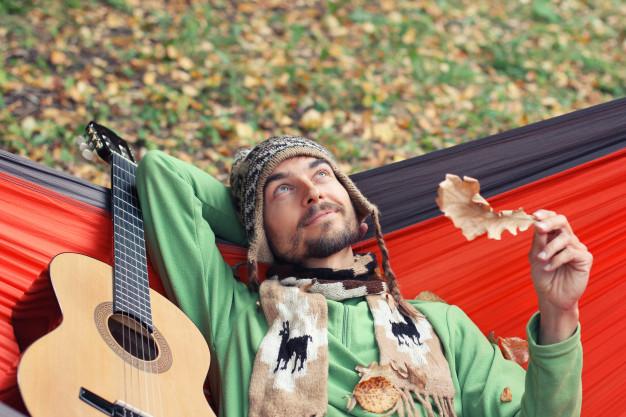 spiller guitar i hængekøje